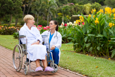 old woman in wheelchair with nurse